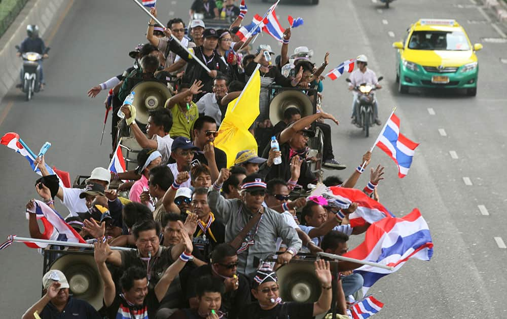 Anti-government protesters riding on a truck wave Thai national flags on their way to the Industry Ministry in Bangkok, Thailand, Wednesday, Nov. 27, 2013 Protesters vowing to topple Thai Prime Minister Yingluck Shinawatra took to the streets for a fourth straight day on Wednesday, declaring they would take over