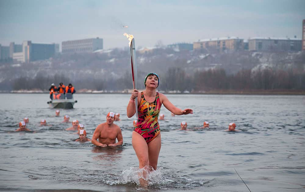 Torch bearer Natalia Usacheva, ice cold water swimmer, exits the Tatyshev Channel of the Yenisei River with an Olympic torch during the Olympic torch relay in Krasnoyarsk, Russia.