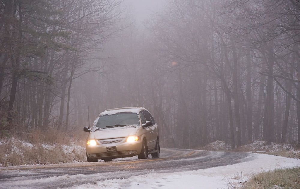 A car travels on Snake Road in Conyngham Township, Pa., as a mixture of rain, freezing rain and sleet fall heavily throughout the area.