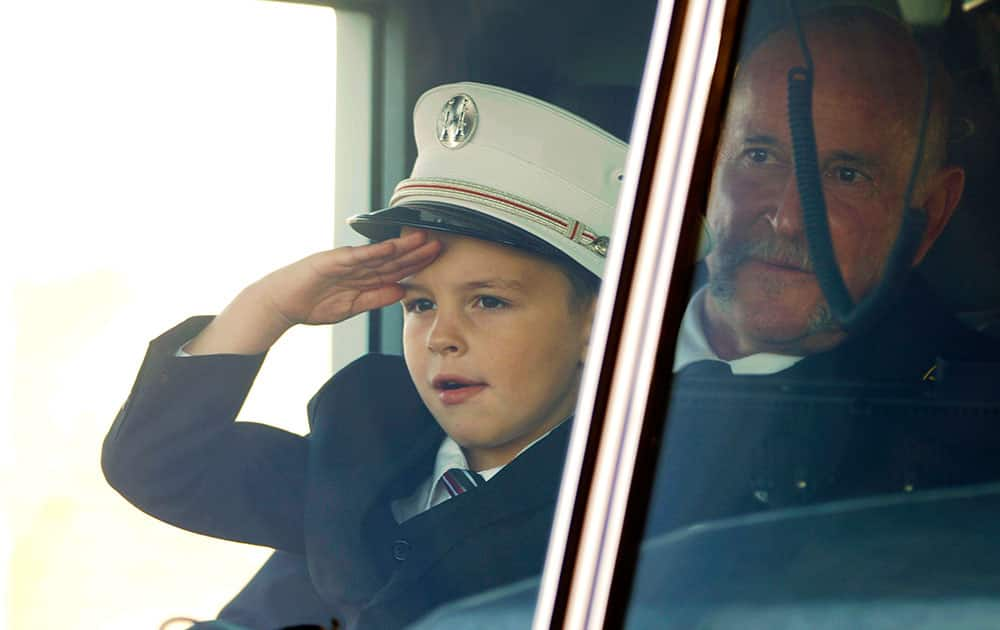 Jack Erickson, the son of Brandon Erickson, salutes firefighters as he sits on the lap of family friend Capt. Scott Kiesig in the Eagle fire truck that was transporting the casket of his father following the Tuesday, Nov. 26, 2013 memorial service at Eagle Christian Church in Eagle, Idaho.