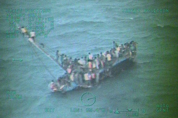This image taken from video made available by the U.S. Coast Guard shows a group of Haitian migrants sitting on the hull of a capsized sailboat near Staniel Cay, Bahamas.