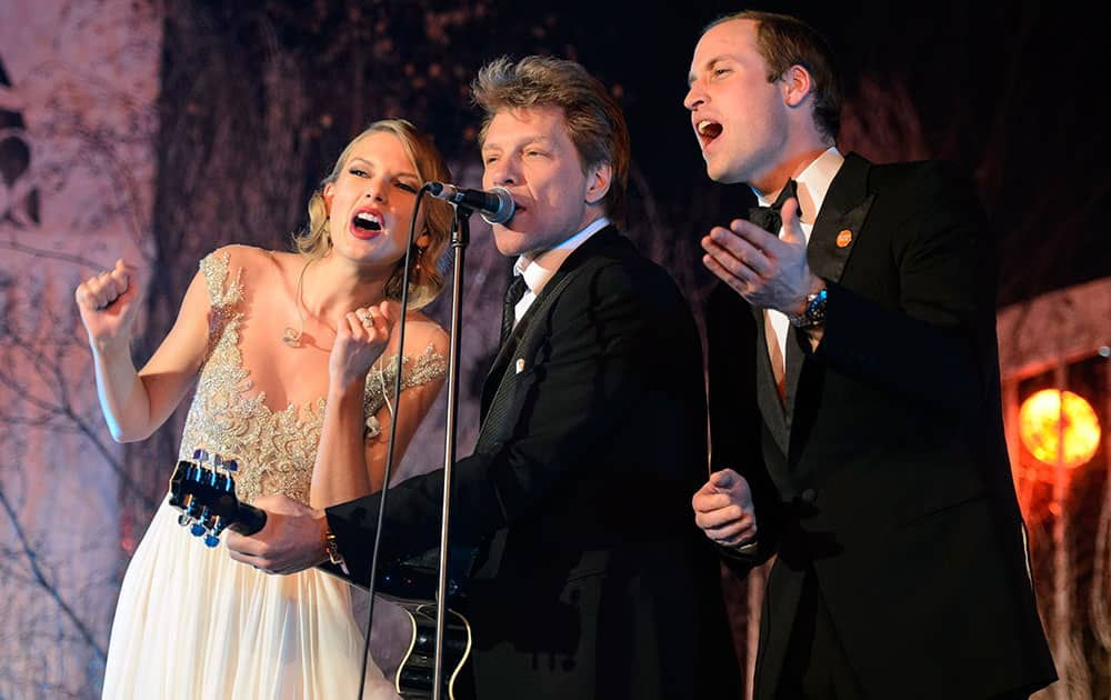Britain`s Prince William, the Duke of Cambridge, right, sings with Taylor Swift, right, and Jon Bon Jovi at the Centrepoint Gala Dinner at Kensington Palace in London.