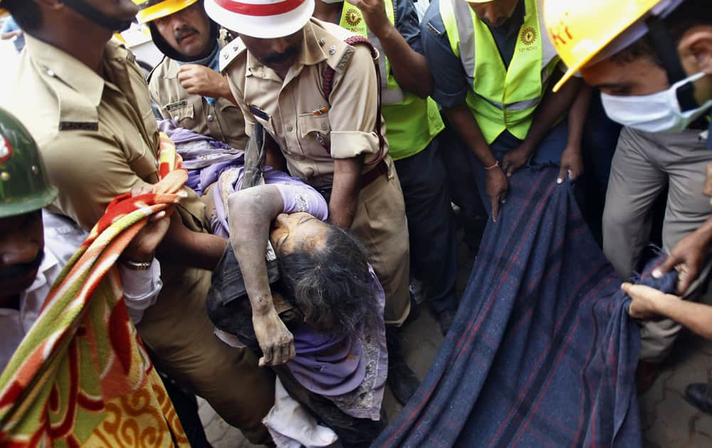 Firemen carry the body of Padma, 45, recovered from the debris of a collapsed house in Bangalore. Five persons including a 18-month old girl were buried alive when their house collapsed after incessant rains over the last few days, authorities said.