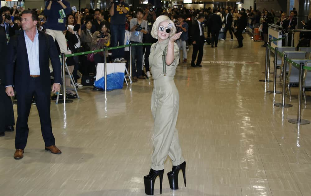 Lady Gaga waves as she is greeted by fans upon her arrival at Narita International Airport in Narita, east of Tokyo.