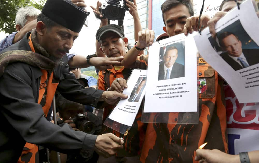 Protesters prepare to burn posters of Australian Prime Minister Tony Abbott during a demonstration against Australia`s alleged wiretapping outside Australian Embassy in Jakarta, Indonesia.