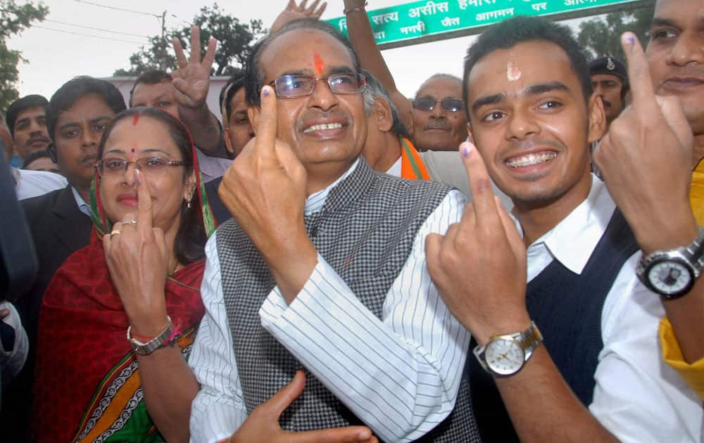 Madhya Pradesh Chief Minister Shivraj Singh Chauhan with his wife Sadhna Singh (L) and son Kartikey Singh Chouhan (R) showing their marked fingers after casting votes for Assembly elections at Jait village in Sehore, Madhya Pradesh.