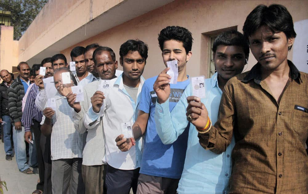 Voters show their identity cards as they wait to cast votes for Assembly elections in Indore.