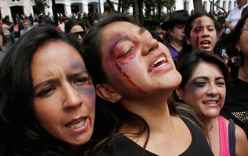 Women with fake bruises painted on their faces protest to mark the Internacional Day for the Elimination of Violence Against Women outside the government palace in Quito, Ecuador.
