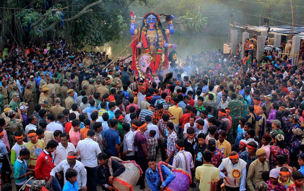 Devotees gather around an idol of Goddess Kali before its immersion in a pond.