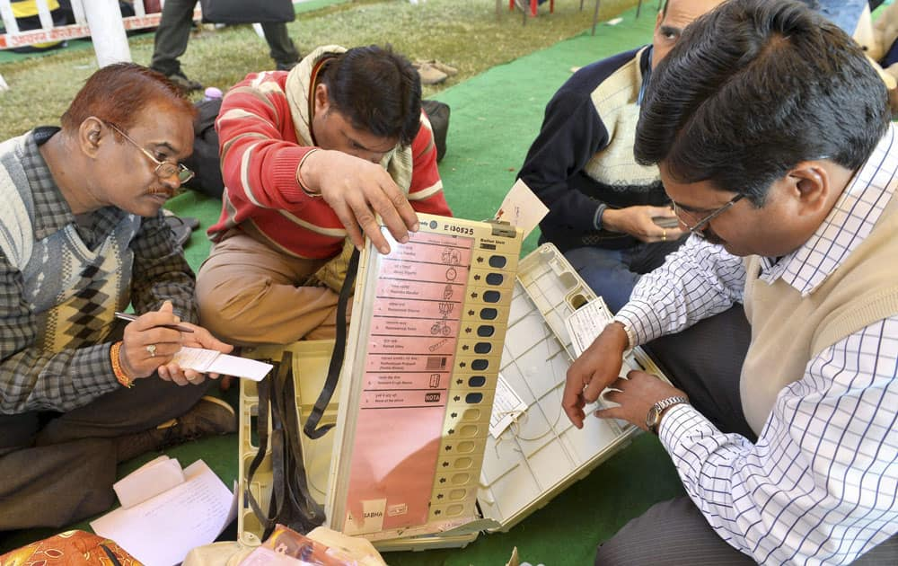 Poll officials check Elctronic Voting Machines (EVM) and other election materials distributed to them before Madhya Pradesh state assembly elections in Bhopal.