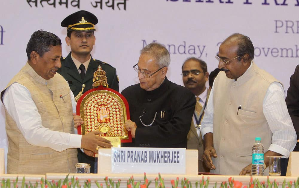 President Pranab Mukherjee receives memonto from Union Minister of State For Micro,Small And Medium Enterprises (Independent Charge)(L), K H Muniyapp during the Coir Board Diamond Jubilee Celebrations in New Delhi.