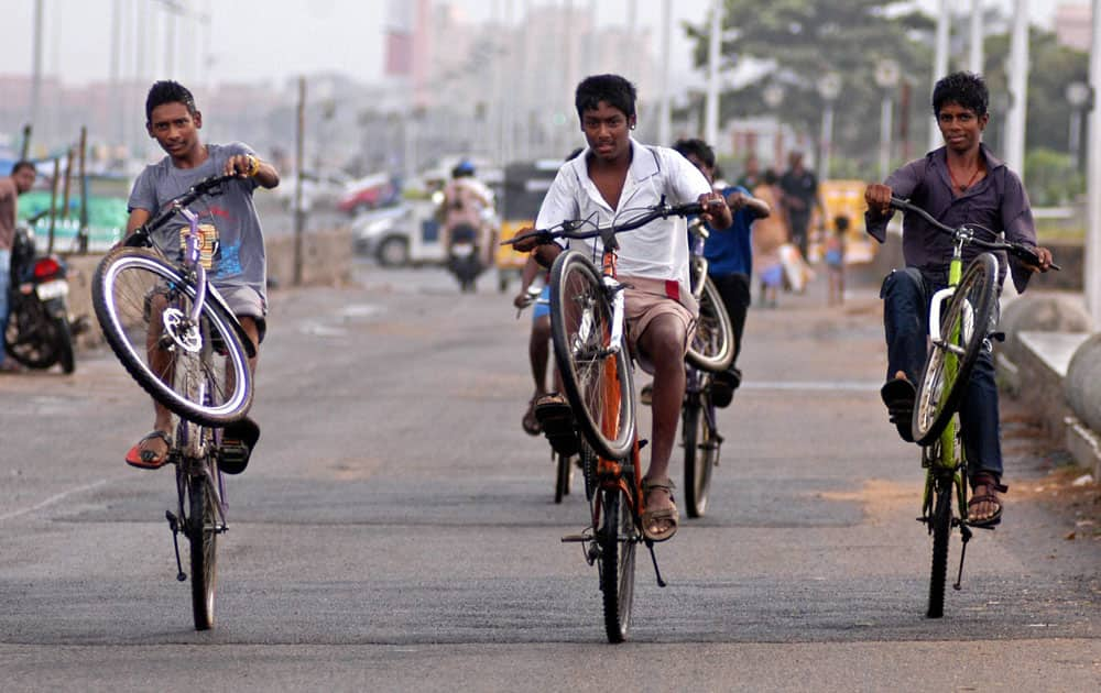 Boys perform stunts on their bicycles in Chennai.