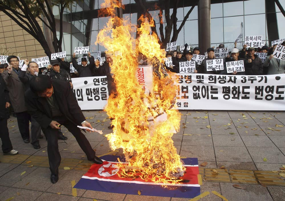 A man burns an effigy of North Korean leader Kim Jong Un and a North Korean flag during a rally to mark the the third anniversary of North Korea's artillery attack on the Yeonpyeong island, in Seoul.