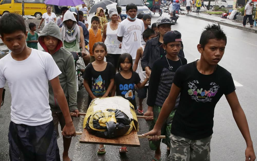 Relatives carry the body of three-year-old Athena Mae Pelingon for burial, at Tacloban city, Leyte province in central Philippines.