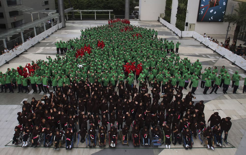Dressed in red, green and black hoodies, 852 Thai students gather together to break the Guinness World Record for forming the largest human Christmas tree in Bangkok, Thailand.