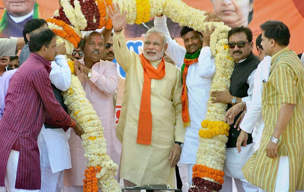 BJP Prime Ministerial candidate Narendra Modi is garlanded during an election rally in Khandwa, Madhya Pradesh.