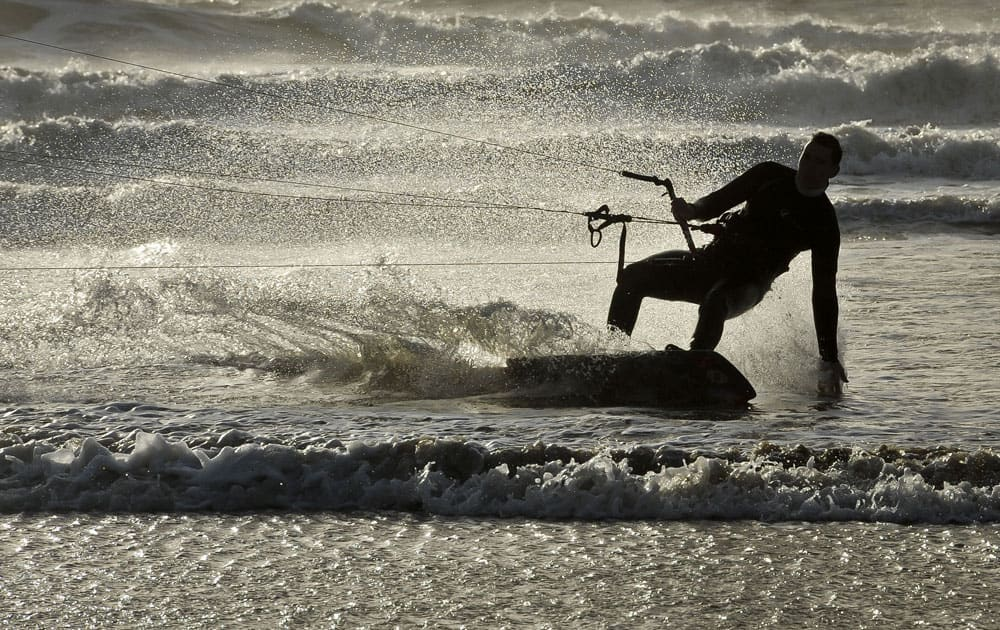 A kite surfer makes the most of the strong winds and dramatic stormy weather at Rest Bay, Porthcawl, Wales.