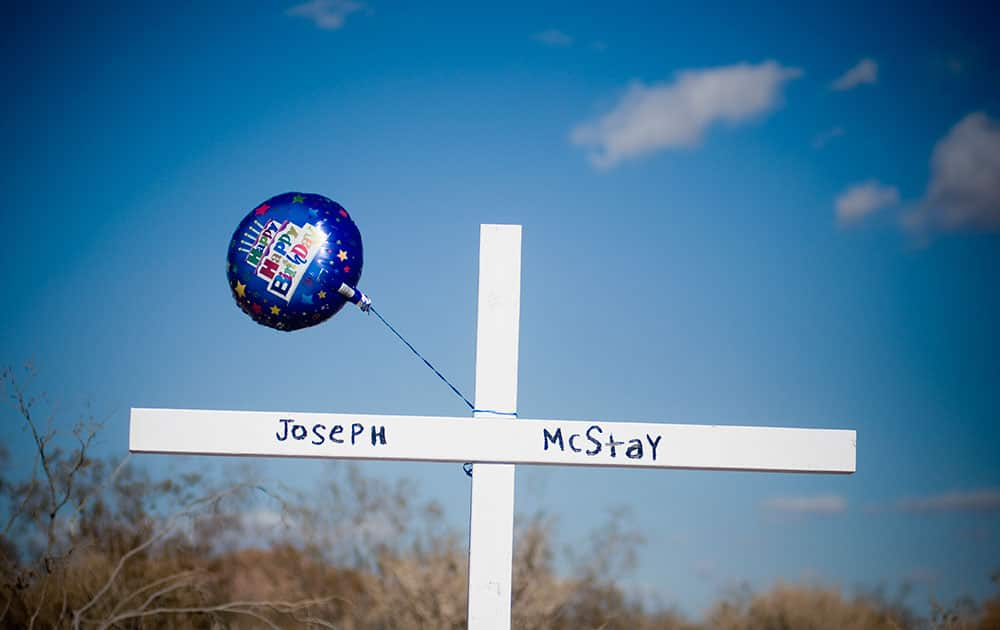 A birthday balloon blows in the wind after it was placed on a memorial cross for Joseph McStay, whose body, along with his wife and two children were found in a shallow grave, in Victorville, Calif.