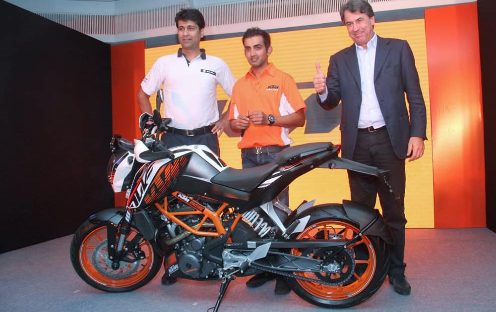 Rajiv Bajaj, MD Bajaj Auto Ltd. and Stefan Pierer, CEO KTM Sport Motorcycles presenting a 'Special Edition' KTM 390 Duke to Indian Cricketer Gautam Gambhir during an event in New Delhi.
