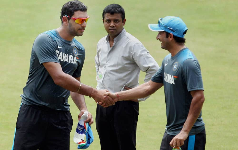 Yuvraj Singh greets Mohit Sharma during a practice session on the eve of the 1st ODI against West Indies at Jawaharlal Nehru Stadium in Kochi.