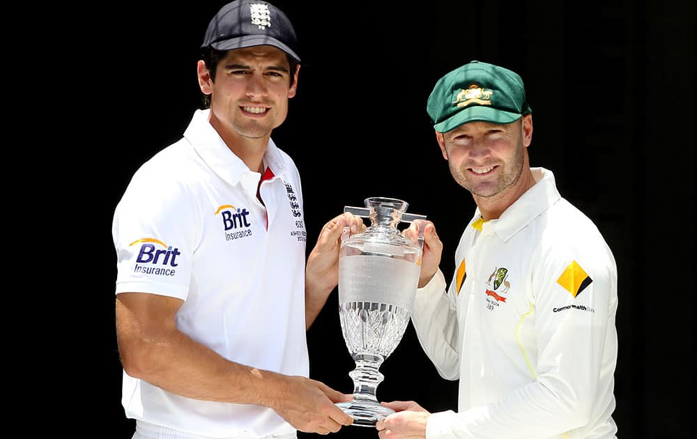 England captain Alastair Cook, left, and Australian captain Michael Clarke pose with the Ashes Trophy on the eve of the first test in the Ashes Series between England and Australia, in Brisbane, Australia.