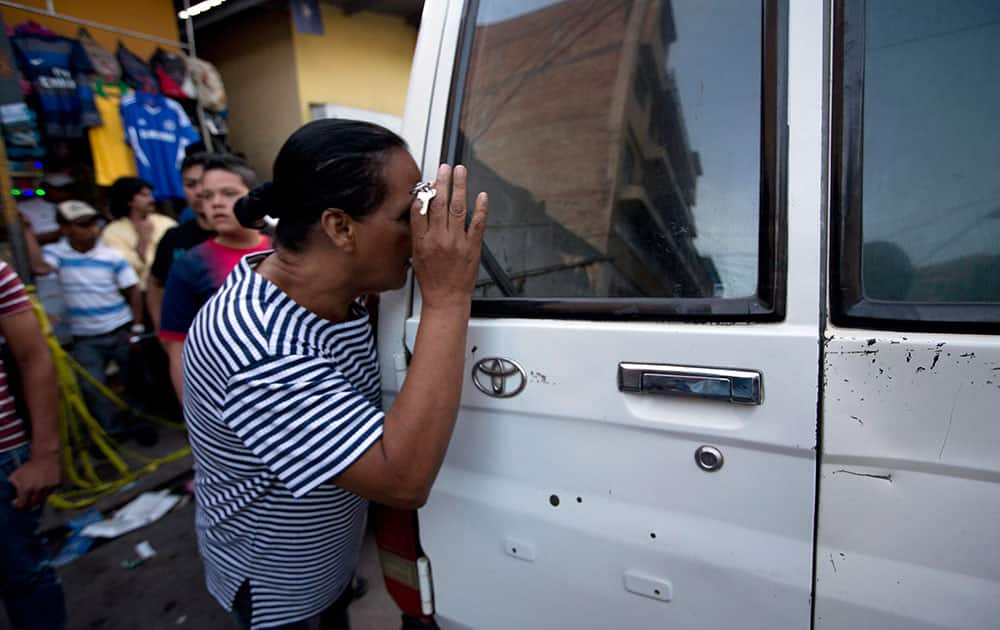 A woman tries to see the body of a taxi driver who was killed in downtown Tegucigalpa, Honduras.