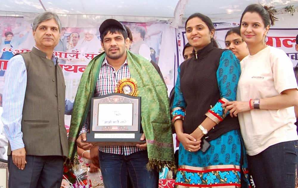 Dr. Rajendra Tonk presents a memento to Olympian Sushil Kumar during a event in Sonipat.