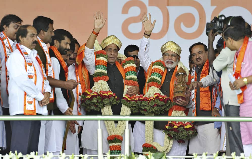Bharatiya Janata Party prime ministerial candidate Narendra Modi and party president Rajnath Singh, wave to their supporters after their felicitation at a public rally in Bangalore.