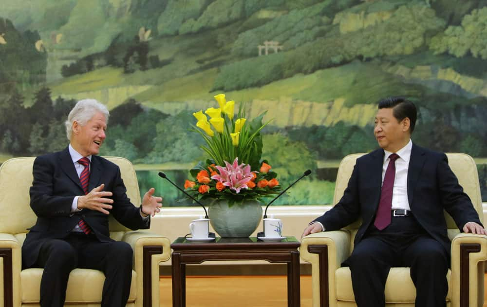 Former US President Bill Clinton, left, speaks to China`s President Xi Jinping during a meeting at the Great Hall of the People, in Beijing.