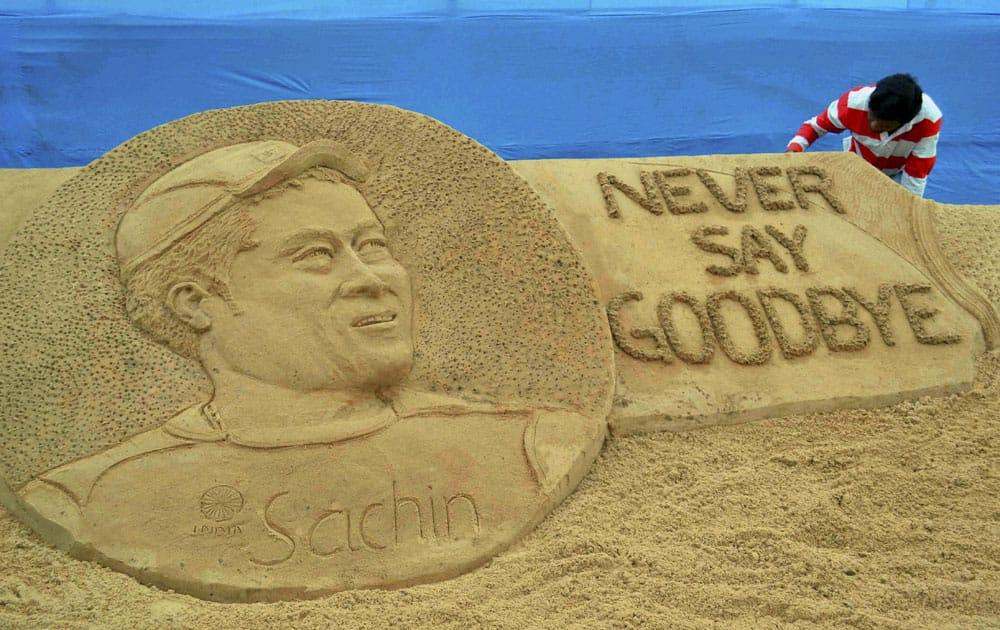 Sand artist Sudarsan Pattnaik giving final touches to the sand sculpture of Sachin Tendulkar at Cuttack in Odisha.