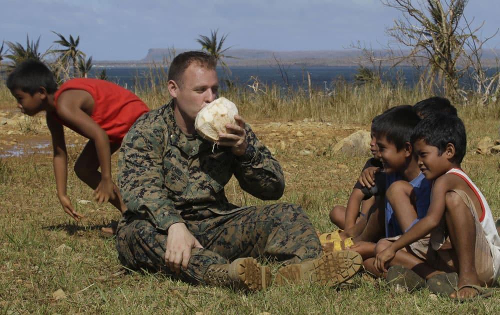 US Marine Maj. John Orio from San Diego, CA, drinks fresh coconut juice upon landing on Manicani island which was isolated by super typhoon Haiyan.