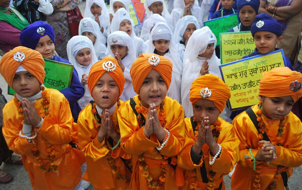 Young Sikhs participate in a religious procession on the eve of the birth anniversary of Guru Nanak in Amritsar.