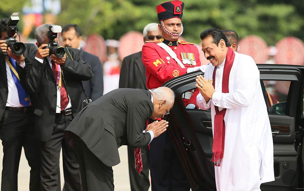 An official greets Sri Lankan President Mahinda Rajapaksa upon his arrival at the opening ceremony of the Commonwealth Heads of Governments meeting, in Colombo, Sri Lanka.