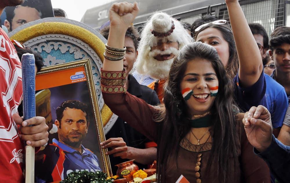 Fans of Sachin Tendulkar celebrate in front of his portrait as they wait in queue to watch Tendulkar's last test match in Mumbai.