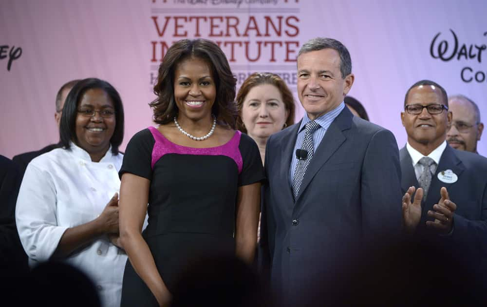 First lady Michelle Obama stands with Disney Chairman and CEO Robert Iger, front right, and veteran cast members before addressing attendees of Disney`s Veterans Institute jobs forum in Lake Buena Vista, Fla.