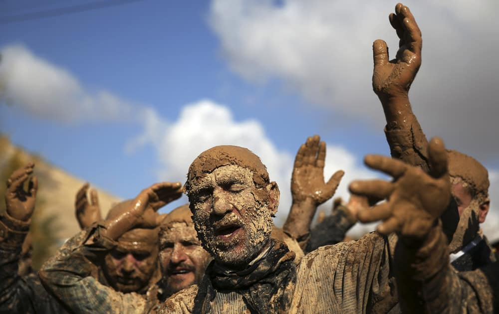 An Iranian Shiite is covered in mud during Ashoura rituals, marking the death anniversary of Imam Hussein, the grandson of Islam`s Prophet Muhammad, at the city of Bijar, west of the capital Tehran, Iran.