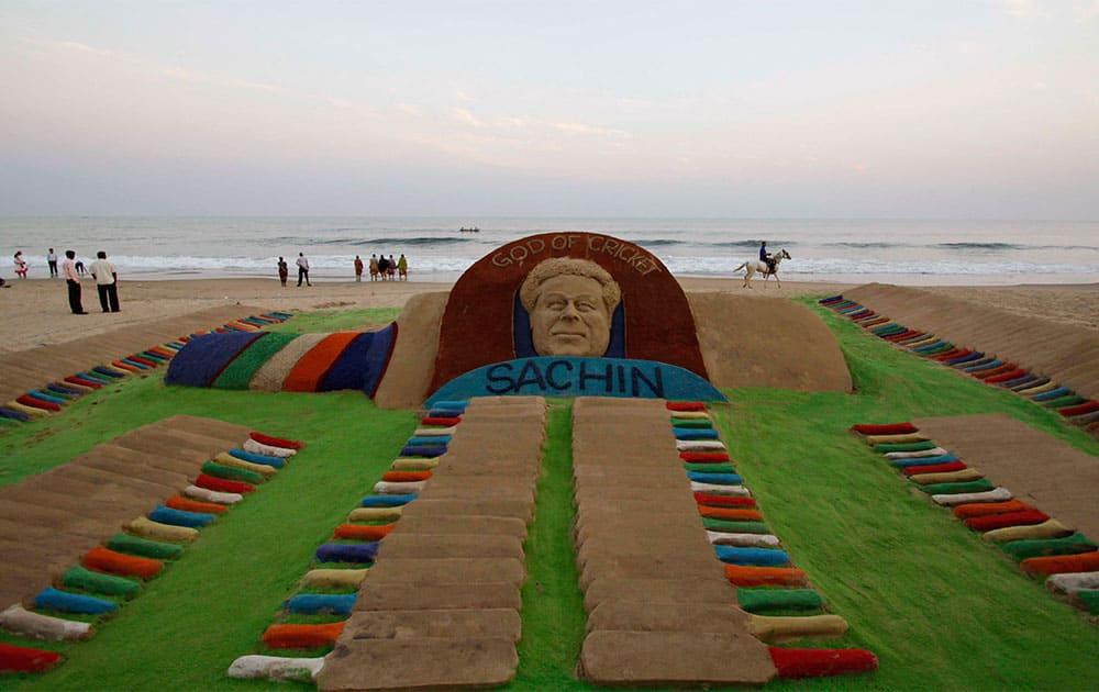 An Indian man rides a horse past a sand sculpture of Indian cricket player Sachin Tendulkar created by Sudarshan Pattnaik on a beach in Puri.