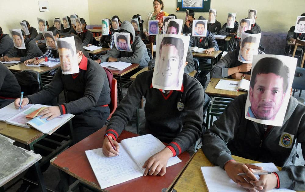 School students fix pictures of Sachin Tendulkar on their faces to pay their respect to him on the eve of Children`s Day in Moradabad.