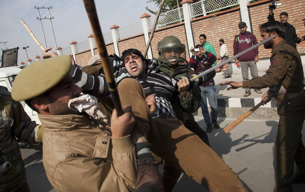 Police men detain Kashmiri Shiite Muslims after they were stopped by police officers during a Muharram procession in Srinagar.