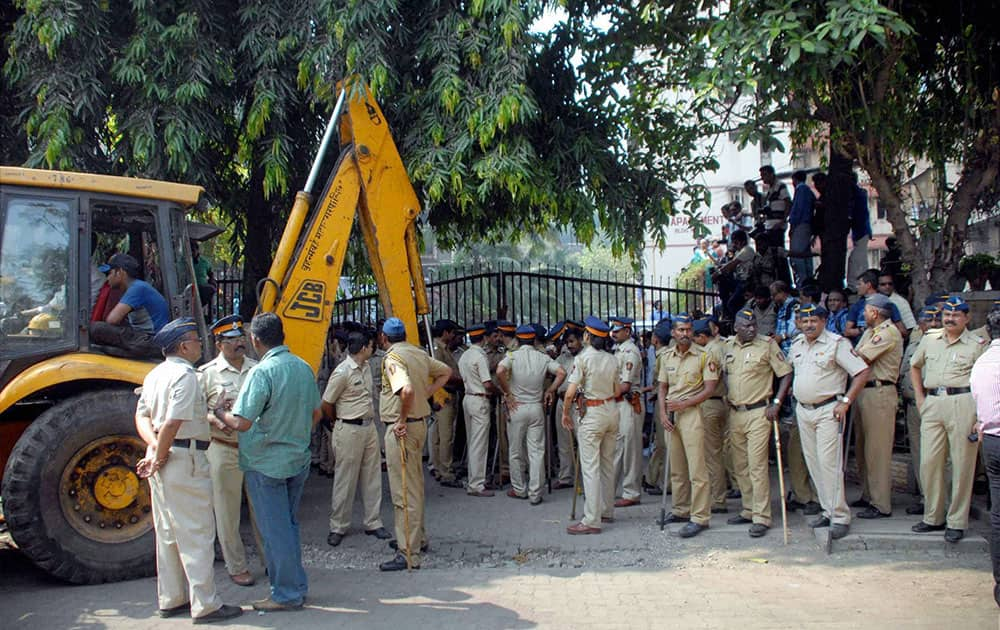 A policeman stands in front of a gate blocked by residents of Mumbai`s Campa Cola housing colony in Mumbai.