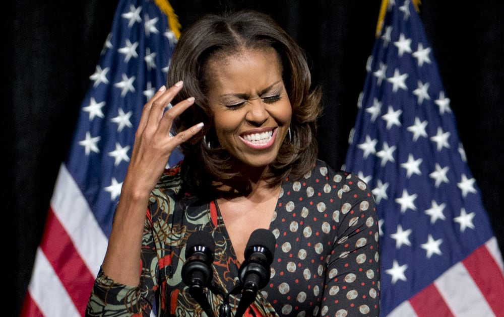 First lady Michelle Obama gestures as he speaks to students about committing to education to create a better future for themselves and their country, at Bell Multicultural High School in Washington.