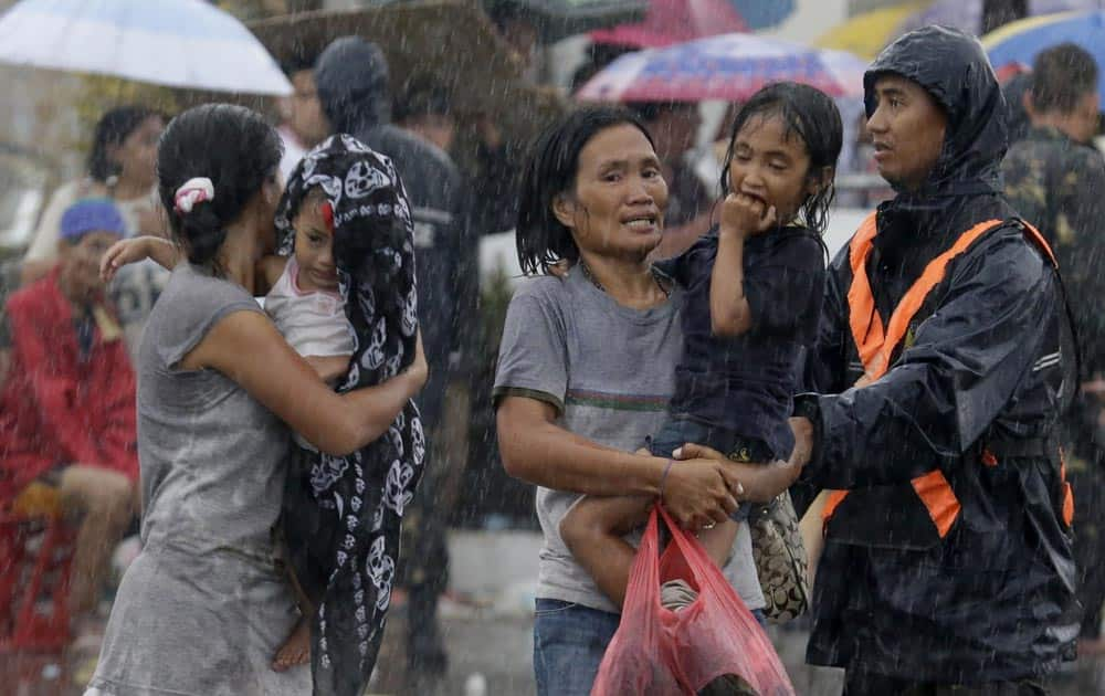 Typhoon survivors rush to board to board a C-130 military transport plane.