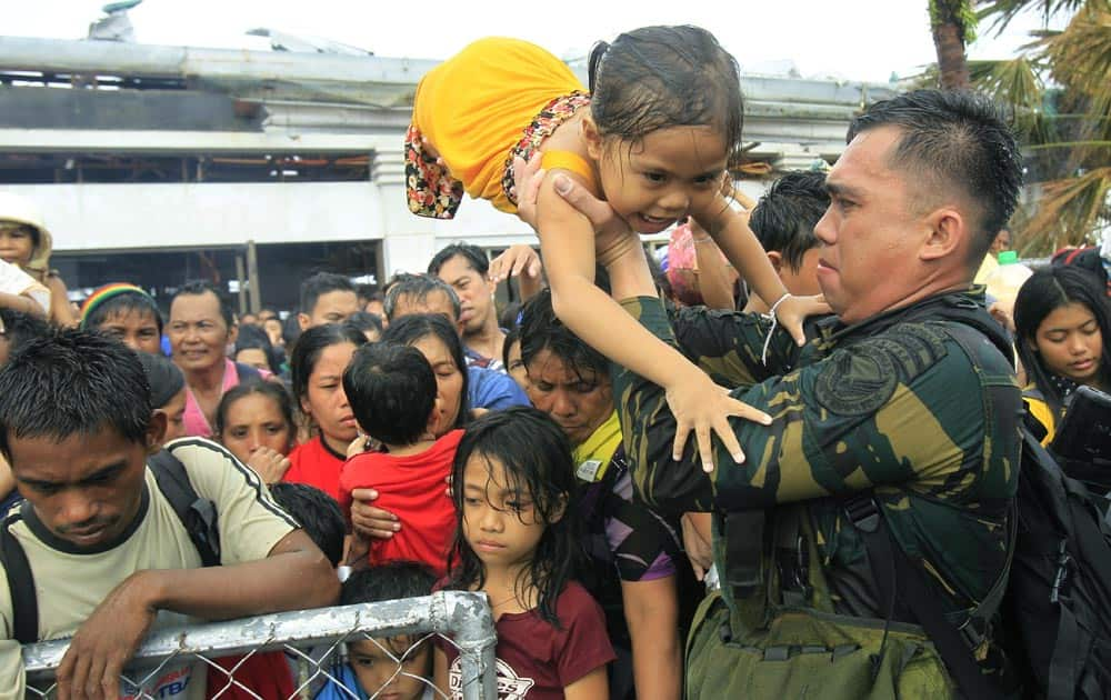 Philippine military personnel try to prioritize children and women first as people wait for evacuation flights in Tacloban, central Philippines.