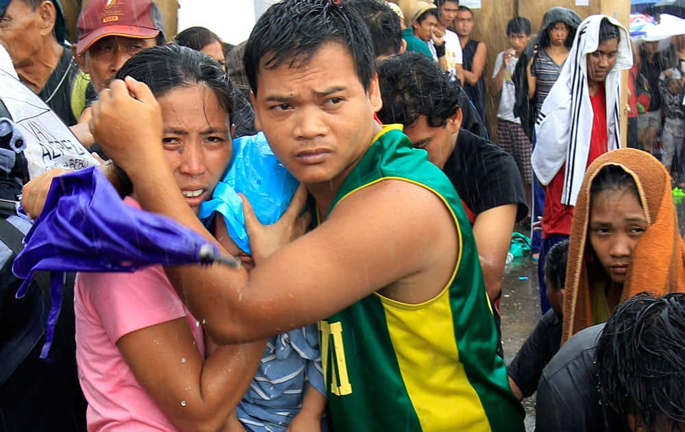 A husband and wife protect their baby from the rain as they wait for an evacuation flight in Tacloban, central Philippines.