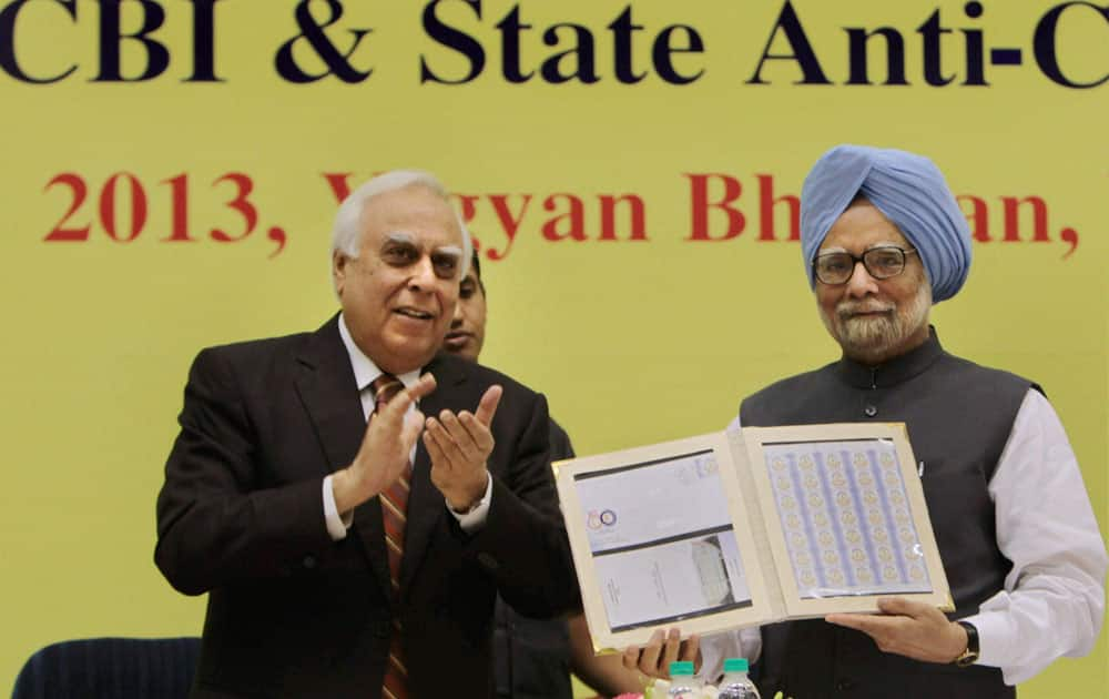 Prime Minister Manmohan Singh releasing a special commemorative stamp as Union Minister for Communications and IT Kapil Sibal looks on during the Central Bureau of Investigation (CBI) conference.