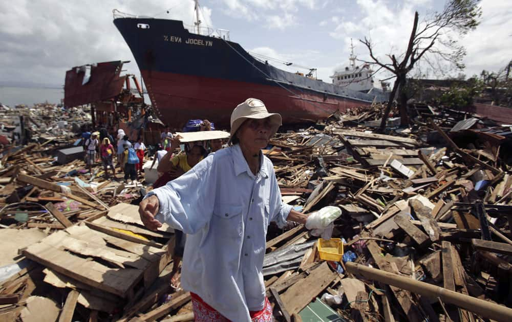 Survivors walk through the rubble of damaged homes and a ship that was washed ashore in Tacloban city, Leyte province, central Philippines.