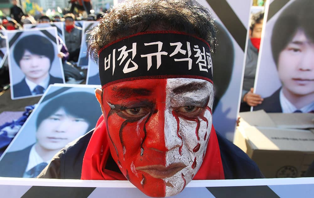 A worker with his face painted, stands in front of portraits of Choi Jong-beom as he participates in a rally against government`s labor policy in front of the Seoul City Hall in Seoul, South Korea.