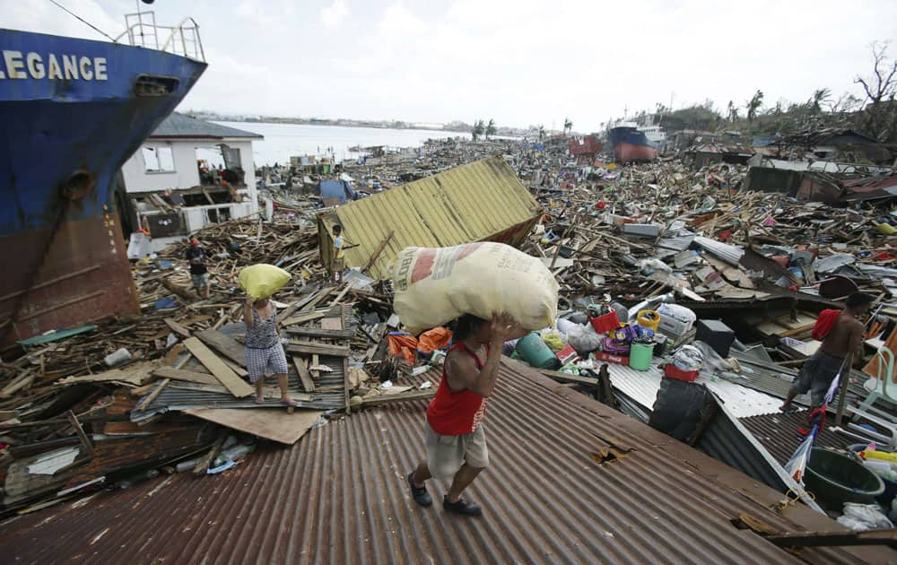 Residents carry relief goods on top of destroyed homes after strong waves caused by Typhoon Haiyan slammed into Tacloban city, Leyte province central Philippines.