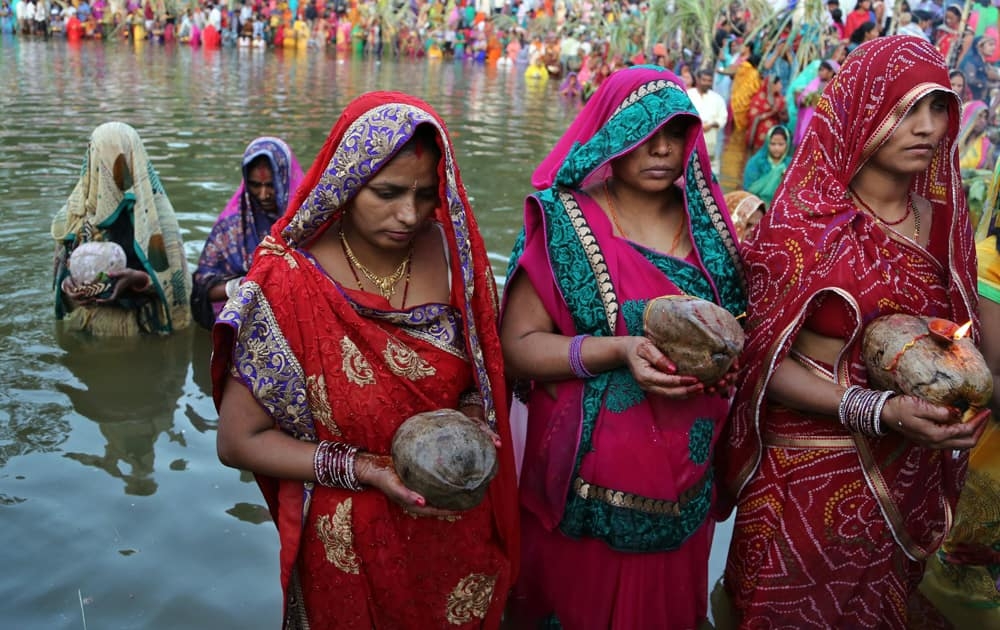 Hindu devotees hold coconuts as they stand in water to perform rituals to the setting sun during Chhath Puja festival in Bangalore.