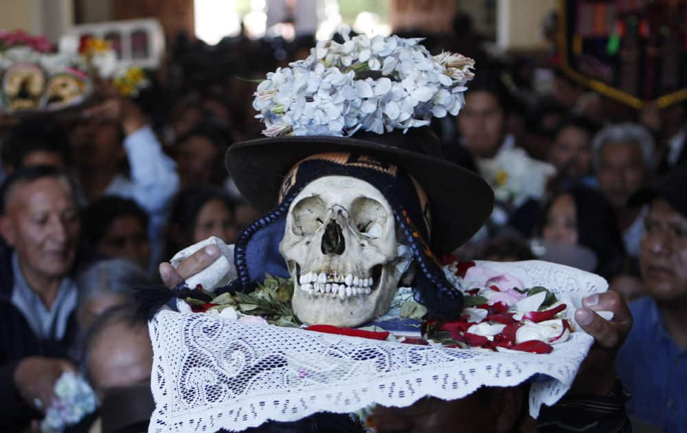 A man carries a decorated human skull or